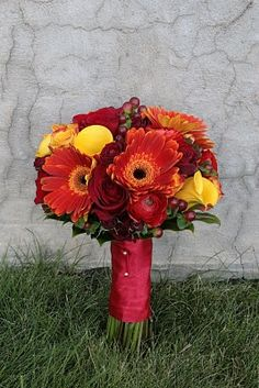 A combination of red roses, orange gerbera daisies, yellow roses and calla lilies, and berries make for a stunning bouquet!