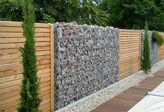 Gabion Wall Stone and Wood Fence. Along the fence line Backyard Fences, Garden Fencing, Fenced In Yard, Mesh Fencing, Garden Trellis, Gabion Retaining Wall, Outdoor Spaces, Outdoor Living, Stone Fence