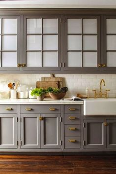 Here's another room enhanced by brass hardware. See how it warms up the gray cabinets? And how about those frosted uppers for those who like the look of glass, but aren't particularly organized?