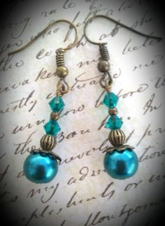 Teal pearl earrings with teal crystals on bronze spacers and