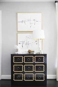 Sally Wheat - Stacked black and white art in gold frames over Dorothy Draper Espana Bunching Chest topped with white Bourgie Lamp.
