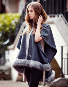 Add a cosy finish to your wardrobe with this grey cape, by Lipsy. Featuring an all round faux fur trim. Make this a must have addition to your Autumn / Winter wardrobe. #getthelook