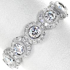 Elegance features seven larger round brilliant diamonds, each surrounded by a dazzling halo of smaller diamonds. The larger diamonds are set in a bright cut milgrain bezel, creating a seamless transition into the halo.  #engagement #wedding #ring www.knoxjewelers.biz
