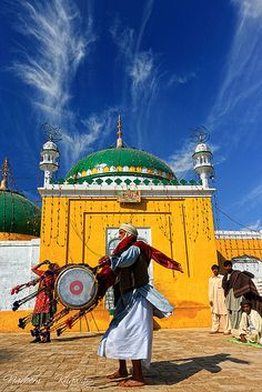 Dance of dreams Drummer is dancing while beating drum outside a shrine  - Pakistan