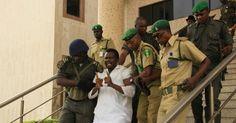 25/jan/2013 - NIGERIA - Edmund Ebiware (centro) é levado para fora do tribunal, em Abuja, Nigéria, depois de ser considerado culpado de ajudar a planejar a explosão de dois carros-bomba na capital da Nigéria em 2010 e condenado à prisão perpétua.Domingo Aghaeze/AP Photo.