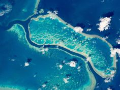 Captured by an astronaut aboard the International Space Station (ISS), shown here are three reefs in Australia's Great Barrier Reef, a natural wonder of the world battling an existential threat caused by warming oceans.