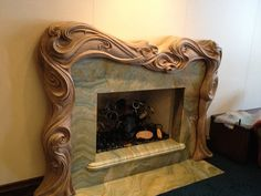 Hand Carved Fire Surround/Mantle A unique one-of-a-kind Art Nouveau(ish) style mantle carved out of laminated walnut wood. This was a design that went through many stages of development via consultations with the clients/designer. From drawing, to clay model, to construction and finally carving, it was a very involved process.