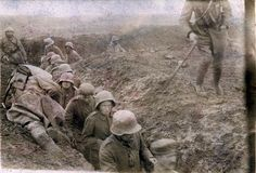 "Nervous and beleaguered German troops file past the body of a French soldier on their way to captivity. Verdun 1916    Nothing on reverse ""Post Card"" - ""Carte Postale"".    Nervous and beleaguered German troops file past the body of a French soldier, killed at the edge of a shallow trench at Verdun, sometime towards the end of 1916."