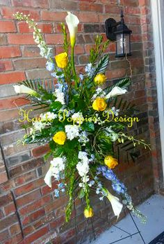 Blue Yellow and White Sympathy Spray in a Medium Size with Calla Lily and Delphinium @ Hautepoppies.com