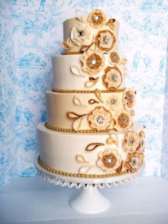 Cake Avenue inspired design in ivory and gold tones. Iced in BC with MMF flowers and leaves.