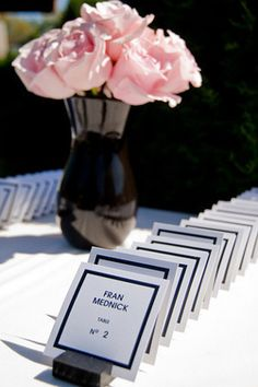 Pink and black coco chanel inspired baby shower escort card table designed to look like perfume cards