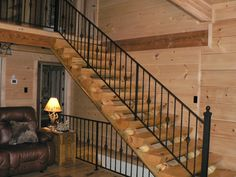 Custom log home wrought iron and half log stairway