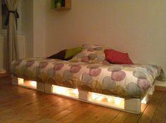 Une palette lit éclairée par une guirlande lumineuse
