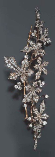 An antique gold, silver and diamond vine brooch, circa 1880. The brooch separates into three smaller pins.