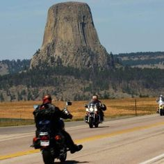 Harleys riding past Devil's Tower National Monument, near Spearfish, SD.  One of the sights Sturgis rally attendees love.