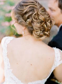 romantic messy loose curls wedding updo with beaded pin