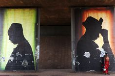 A woman stands in front of a poster in Bamako, Mali, February 21, 2014. REUTERS/Joe Penney