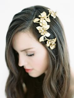 COLETTE GOLD BLOSSOM BRIDAL COMB - The delicate arc of a naturalistic brass branch supports a splendid series of flowers, making this wedding hair comb a true statement headpiece. With a traditional gown or a modern look, the bold golden almond flowers (each centred on a light gold Swarovski crystal) make a gorgeous finish to the wedding ensemble to which you've given so much thought.