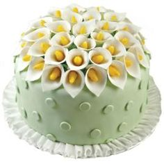 This fondant cake is a lesson in complementary colors. The pure white lily petals and ruffled border stand out against the spring green fondant polka dots and sunny yellow flower centers for all the texture and beauty you could want!