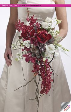 Moss branches combine with wired flexible vine create the cascading shaped bouquet containing lotus pods, pincones, red peonies and James Story Orchids. Floral design by Cindy Tole. Photography by Ron Derhacopian. #wedding #centerpieces #bouquets.