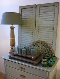 interieur in olijfgroen; antieke ladenkast, oude louvreluiken, hekje, balluster als lampvoet en  gemberpotjes