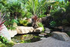 Landscaping with boulders can provide a spectacular outlet. Landscaping with boulders requires a good bit of advance planning due to the heaviness of these objects. Tropical Landscaping, Pond Landscaping, Backyard Water Feature, Waterfalls Backyard, Landscaping With Boulders, Garden Pond Design, Landscaping With Rocks, Pretty Gardens, Tropical Landscape Design