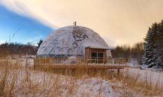 Una casa autosuficiente en el ártico, con un cúpula geodésica que la rodea y le permite cultivar sus propios alimentos, paneles solares para su energía.