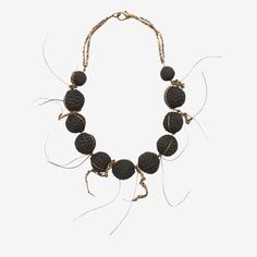 This necklace is inspired by organic forms. The handmade ceramic beads are combined with golden threads, creating a modern piece that can be part of many different styles, worn from morning to evening. Most objects designed by ceramist Laura Venizelou are made of black clay. She began using it because she was intrigued by its rough, almost volcanic texture. As she states, it is the material itself that leads her to shape forms, as an infinite source of inspiration.