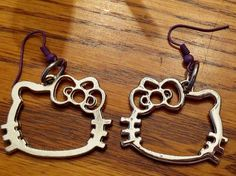 Handmade Silver Hello Kitty Earrings  These 25x30mm silver charms came from old Hello Kitty purses.  The charms look brand new!  I put them on pretty purple hooks!  Dangle length is approx 43mm long.