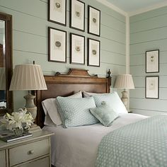 Beautiful sea green bedroom with horizontal wood panel walls! We love the non-painted natural wood tones of the headboard and mirror frame!
