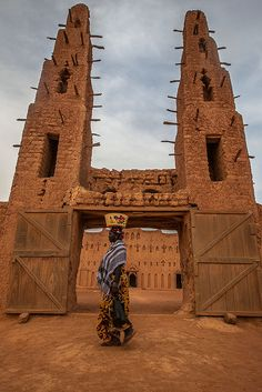 Africa  A woman with a pot on her head at the main entrance of the great mud mosque of Bani, Sahel, northern Burkina Faso