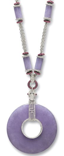 LAVENDER JADEITE, RUBY AND DIAMOND PENDANT NECKLACE The pendant set with a translucent lavender jadeite disc, to a surmount of geometrical motif set with circular-cut diamonds and rubies; the necklace set with six lavender jadeite tubular beads of matching colour and translucency, decorated by rondelles set with circular-cut diamonds and rubies; the rubies and diamonds together weighing approximately 3.50 and 2.70 carats respectively, mounted in 18 karat white gold, length approximately…