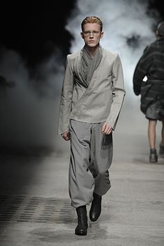 Alternating between black and ash gray, Damir Doma uses the fall season as the perfect opportunity to pack the volume back on. Creating his own bubble away from the world, Doma moves to cloak his man from the elements with meticulously constructed layers of seamless draping. Meanwhile, robe-like outerwear and billowing shapes act as a...[ReadMore]