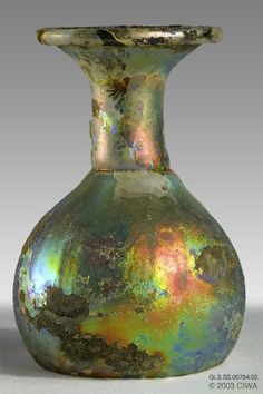 Iridescent sprinkler flask,The glass is very thin and fragile. The bottom is kicked, with a deep conical depression. Syria, Eastern Roman Empire, late third to early fourth century AD. history of glass Glass Vessel, Glass Ceramic, Glass Art, Antique Bottles, Antique Glass, Glass Bead Game, History Of Glass, Vases, Ancient Artifacts