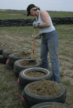 Nicole Chayka filling tires at Eco Ark Saskatchewan's Earthship build, photo by Monica Holy