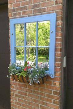vieille fenêtre transformée en miroir et avec une jardinière en tant que déco murale extérieure