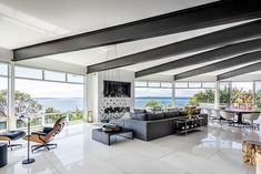 Large steel beams, quartz stone tiles, gas fireplace, and expansive windows overlooking the view of the water
