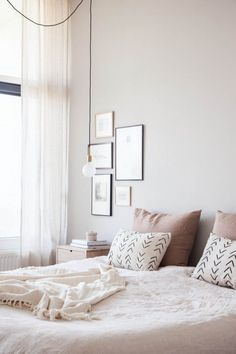 Interior design inspiration a neutral yet feminine bedroom with art collection and cozy comfort detailing.                                                                                                                                                                                 More