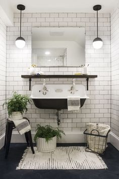 monochrome bathroom, white subway tiles, black sink, plants, white rug, black pendants