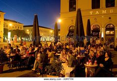 People sitting outside cafe Tambosi near the Hofgarten and the Theatiner church Munich Bavaria Germany Europe - Stock Image