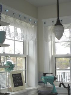Lace Curtains hung with glass knobs. Crystal knobs from a set of shower curtain rings found at dollar store. Unscrew the curtain hangers and hot-glue knob to window trim.