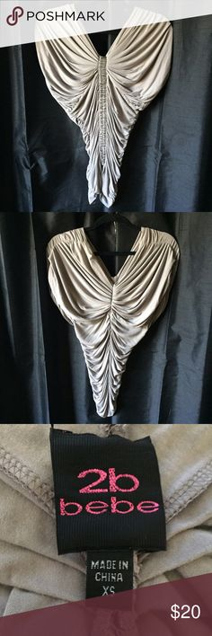 BEBE 2B ruched top This top can be dressed up with a skirt and heels for the club or dressed down with jeans for the weekend. Good condition except for a couple of loose threads on embellishment (see picture) and a bit of fading. bebe Tops Blouses