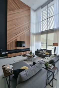 Wil's 11 Residence: living room with a double volume wood wall feature matched with sheer curtains - CAANdesign | Architecture and home design blog
