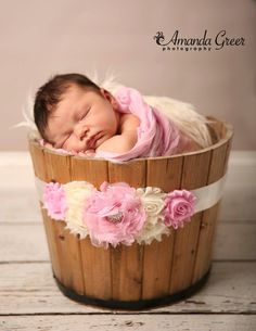 Newborn girl in a bucket with pink accents from a maternity belly sash
