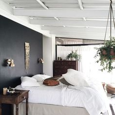 @citysage: the stark contrast of peaceful linens against a sultry black accent wall | domino.com