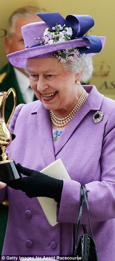 Pretty in purple: Queen Elizabeth II stands out in vibrant purple as she holds the Gold Cup after Ryan Moore riding Estimate won The Gold Cu...