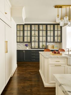Pretty transitional farmhouse kitchen with a wall of glass cupboards! Designed by Carrie Hatfield