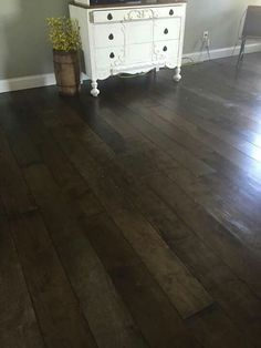 Sheets of 1/2 inch birch plywood (best kind available) cut into planks. Multiple coats of stain (minwax brand - Jacobean) and multiple coats of clear poly. Gym Floor Poly works best.  Black stripes in between boards so for doesn't show underneath.  Hold up?  Use air compressor to nail down in 18g pin nails.