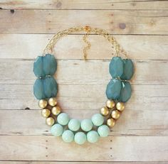 Bridesmaids in mismatched dresses? Tie them together with a statement necklace like this mint, ocean blue and gold one.