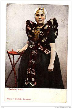 Vrouw in Axelse streekdracht. De vrouw draagt over de ondermuts en het oorijzer een 'trekmuts'. Ze draagt 'dubbele strikken' (dubbele, klaverbladvormige gouden oorijzerhangers) aan de 'krullen' (oorijzeruiteinden) van het oorijzer. Tussen de 'krullen' zijn twee gouden mutsenspelden in de muts gestoken. 1894-1905 #Axel